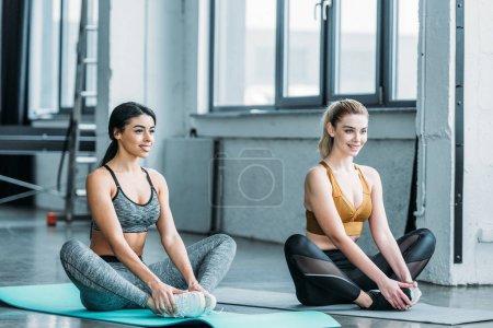 Photo pour Belle souriante jeunes sportives multiraciales formation sur les tapis de yoga dans la salle de gym - image libre de droit