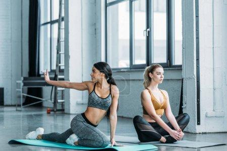 Photo pour Belles jeunes femmes multiethniques dans la formation de sportswear sur tapis d'yoga dans une salle de sport - image libre de droit