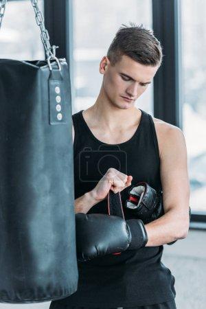 Photo pour Sérieux jeune sportif portant un gant de boxe dans la salle de gym - image libre de droit