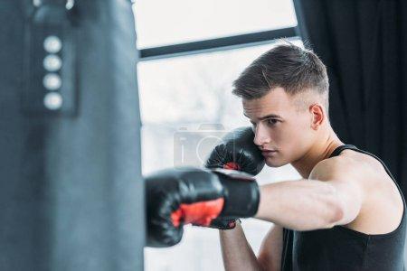 Photo pour Concentré de jeune homme sportif avec sac de boxe au gymnase de boxe - image libre de droit