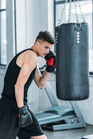 Photo for Athletic young man in boxing gloves training with punching bag in gym - Royalty Free Image