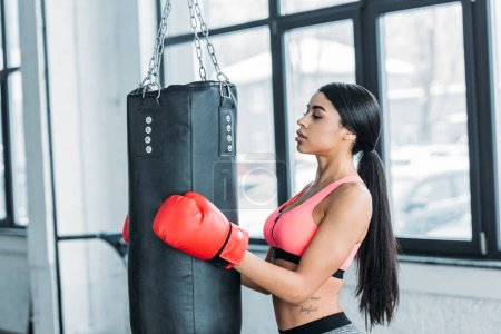 Photo for Side view of young african american sportswoman in boxing gloves holding punching bag in gym - Royalty Free Image