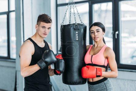 Photo pour Boxeurs masculins et féminins dans des gants de boxe debout près du sac de boxe et regardant la caméra dans la salle de gym - image libre de droit
