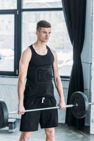 Photo for Concentrated young athlete lifting barbell and looking away in gym - Royalty Free Image