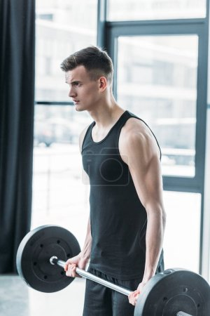 Photo for Concentrated young sportsman lifting barbell and looking away in gym - Royalty Free Image