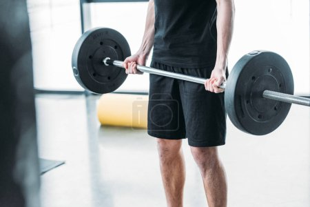 Photo for Cropped shot of young man in sportswear lifting barbell in gym - Royalty Free Image