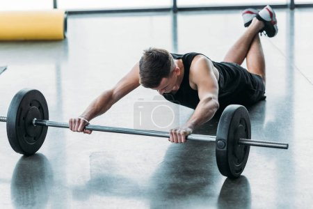 Photo for Sporty yougn man lying and training with barbell in gym - Royalty Free Image