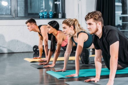 multiethnic athletic young men and women exercising on yoga mats and looking away in gym