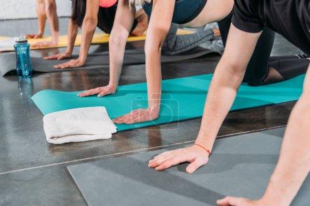 Foto de Recortada de tiro de la gente joven haciendo ejercicio en esteras de la yoga en la gimnasio - Imagen libre de derechos