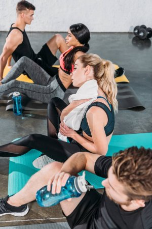Photo for Sporty young people resting on yoga mats after workout in gym - Royalty Free Image
