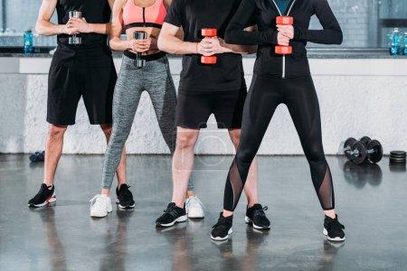 Photo pour Recadrée tir des jeunes en formation de sportswear avec haltères en gym - image libre de droit