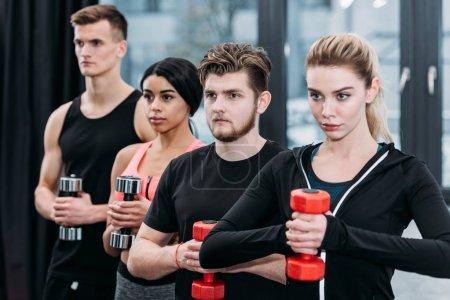 Foto de Amigos jóvenes deportivos multiétnicos sosteniendo pesas y mirando lejos en gimnasio - Imagen libre de derechos