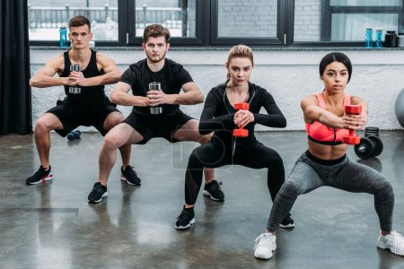 athletic young men and women exercising with dumbbells and looking at camera in gym
