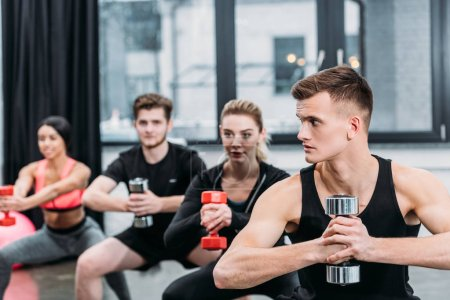 athletic young men and women exercising with dumbbells in gym