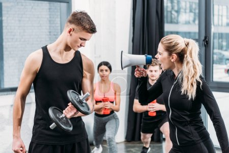Photo for Sportswoman with megaphone yelling at young man training with dumbbell in gym - Royalty Free Image