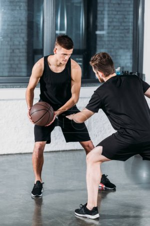 Photo for Athletic young male friends in sportswear playing basketball in gym - Royalty Free Image