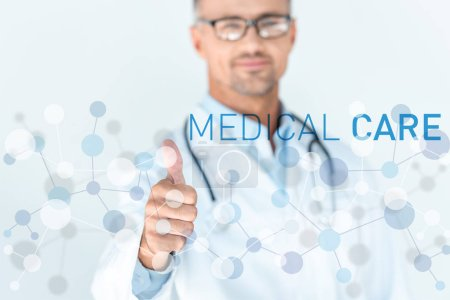 Photo for Selective focus of handsome doctor in glasses with stethoscope on shoulders showing thumb up with medical care interface - Royalty Free Image