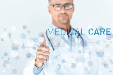 Foto de Enfoque selectivo del apuesto doctor en vasos con estetoscopio sobre hombros mostrando pulgar con atención médica - Imagen libre de derechos