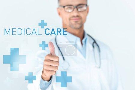 Foto de Enfoque selectivo del apuesto doctor en vasos con estetoscopio sobre hombros mostrando pulgar para arriba con el deletreado de la atención médica - Imagen libre de derechos