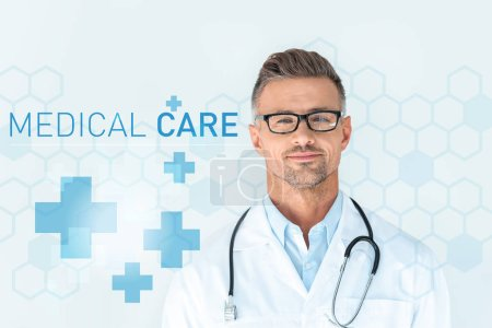 Photo for Handsome doctor in glasses with stethoscope on shoulders looking at camera with medical care lettering - Royalty Free Image