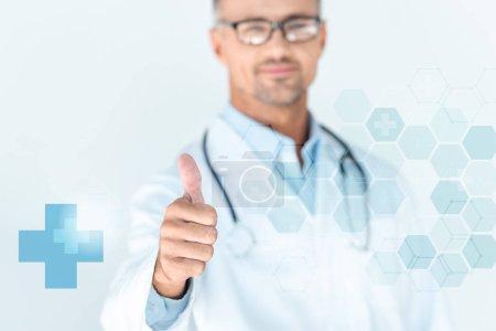 Foto de Enfoque selectivo del apuesto doctor en gafas con estetoscopio sobre hombros mostrando pulgar con interfaz médico - Imagen libre de derechos