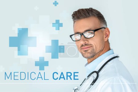 Photo for Portrait of handsome doctor in glasses with stethoscope on shoulders looking at camera isolated on white with medical care lettering - Royalty Free Image