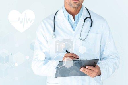 Photo pour Image recadrée de docteur avec stéthoscope sur épaules écrire quelque chose dans le presse-papier blanc avec du rythme cardiaque et medical interface - image libre de droit