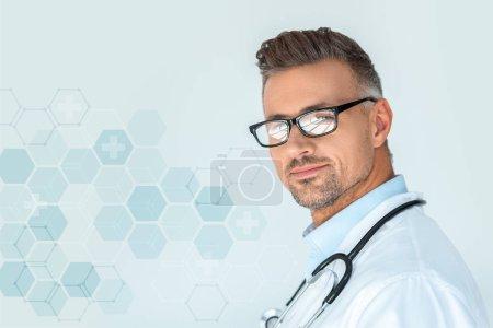 Photo pour Portrait du beau docteur dans des verres avec le stéthoscope sur les épaules, regardant la caméra isolé sur blanc avec interface médicale - image libre de droit