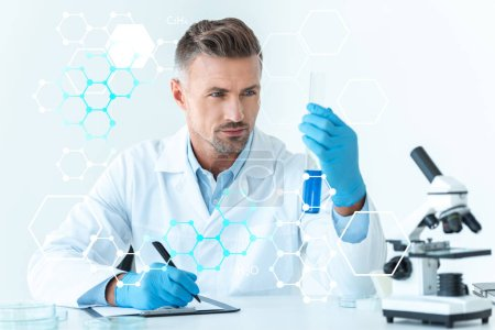 Photo for Handsome scientist looking at test tube with blue reagent isolated on white with medical symbols - Royalty Free Image