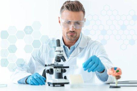 Photo pour Mise au point sélective du beau scientifique en protection lunettes expérience prise au microscope isolé sur blanc avec symboles médicaux - image libre de droit