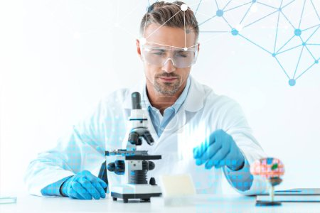 Photo for Selective focus of handsome scientist in protective glasses making experiment with microscope isolated on white with medical symbols - Royalty Free Image
