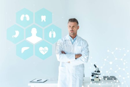 Photo for Handsome scientist standing with crossed arms near table isolated on white with medical interface - Royalty Free Image