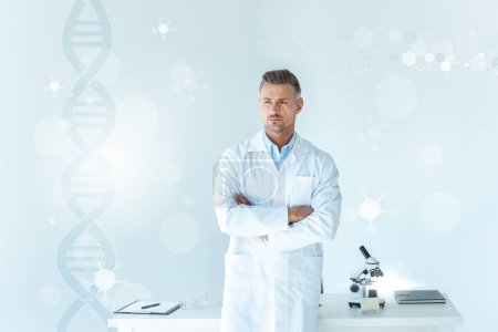 Photo for Handsome scientist standing with crossed arms near table on white with dna - Royalty Free Image