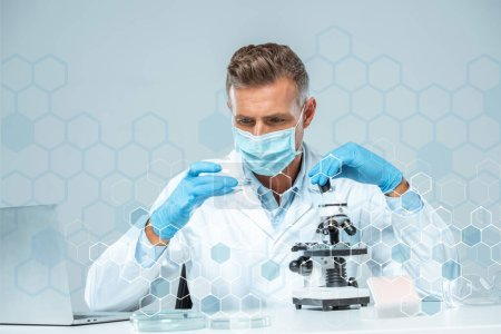Photo for Handsome scientist in medical mask and medical gloves making experiment - Royalty Free Image
