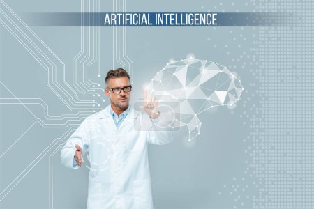 Photo for Handsome scientist in glasses touching brain interface isolated on grey, artificial intelligence concept - Royalty Free Image