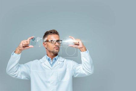 Photo pour Beau scientifique en lunettes tenant l'interface médicale isolée sur gris, concept d'intelligence artificielle - image libre de droit