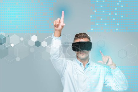 Photo for Scientist in virtual reality headset touching medical interface isolated on grey, artificial intelligence concept - Royalty Free Image