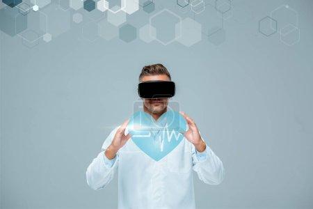 Foto de Científico en el casco de realidad virtual con corazón con latidos aislados en gris, concepto de inteligencia artificial - Imagen libre de derechos