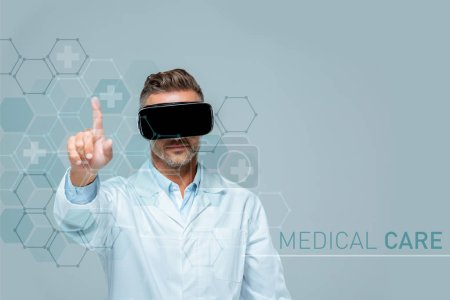 Photo for Scientist in virtual reality headset touching medical care interface with finger isolated on grey, artificial intelligence concept - Royalty Free Image