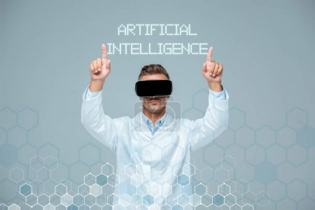 Photo for Scientist in virtual reality headset touching artificial intelligence lettering with two fingers isolated on grey - Royalty Free Image