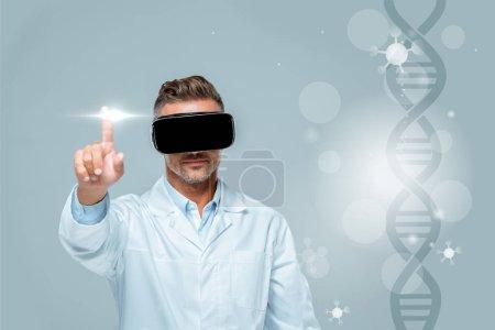 Photo pour Scientifique au casque de réalité virtuelle toucher medical interface avec l'ADN isolé sur gris, concept d'intelligence artificielle - image libre de droit