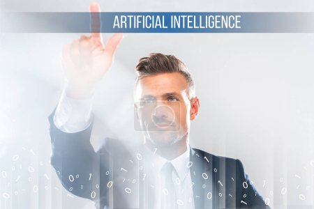 handsome businessman in suit touching artificial intelligence lettering isolated on white