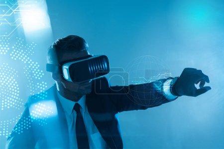 Foto de Empresario en casco de realidad virtual aislado en azul, concepto de inteligencia artificial - Imagen libre de derechos