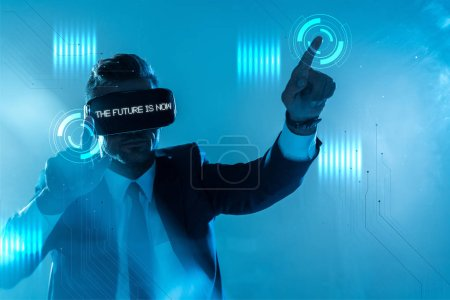 "Photo for Businessman in suit and virtual reality headset with ""choose your future"" lettering touching something isolated on blue, artificial intelligence concept - Royalty Free Image"