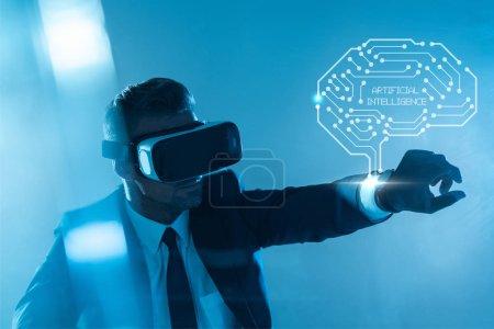 Foto de Empresario en casco de realidad virtual con cerebro aislado en azul, concepto de inteligencia artificial - Imagen libre de derechos