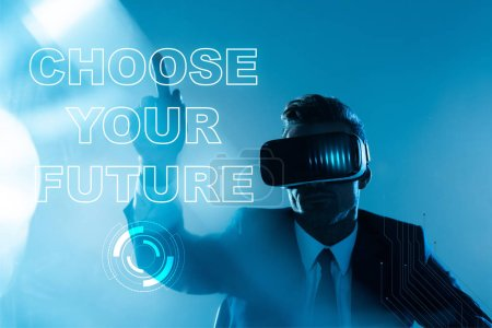 "Photo for Businessman in virtual reality headset pointing on ""choose your future"" lettering isolated on blue, artificial intelligence concept - Royalty Free Image"