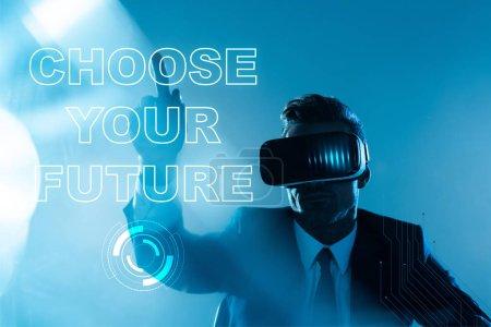 """Foto de Empresario en casco de realidad virtual en """"Elige tu futuro"""" letras aisladas en azul, concepto de inteligencia artificial - Imagen libre de derechos"""