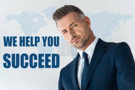 """Photo pour Vue en angle bas de bel homme d'affaires regardant la caméra isolée sur blanc avec lettrage """"nous vous aidons à réussir"""" - image libre de droit"""