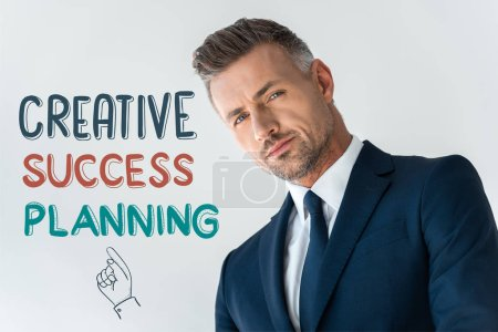 Photo for Low angle view of handsome businessman looking at camera isolated on white with creative success planning - Royalty Free Image