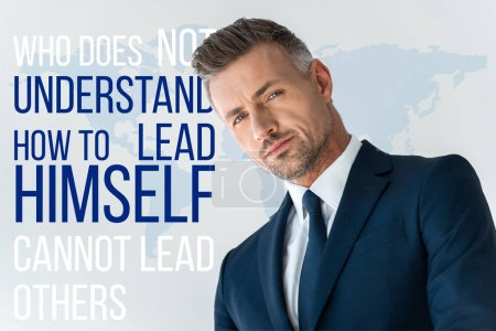 """Photo for Low angle view of handsome businessman looking at camera isolated on white with """"who does not understand how to lead himself cannot lead others"""" lettering - Royalty Free Image"""